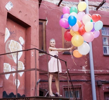 young woman with colorful balloons on a street - outdoors photo