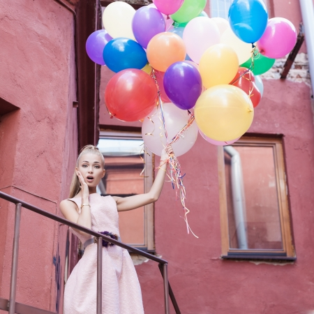 colorful dress: young woman with colorful balloons surprised on a street - outdoors