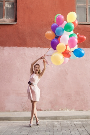 Happy young woman with colorful balloons on a street - outdoors photo