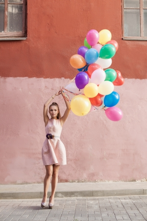 Happy young woman holding colorful balloons on a street - outdoors photo