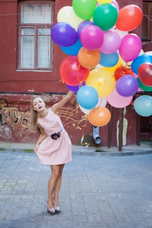 blond woman with balloons, urban scene, outdoors photo