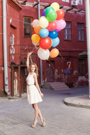windy city: Young woman with colorful latex balloons, urban scene, outdoors Stock Photo