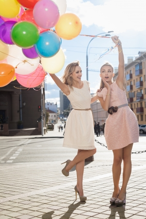 Two young blond women with colorful latex balloons, urban scene, outdoors