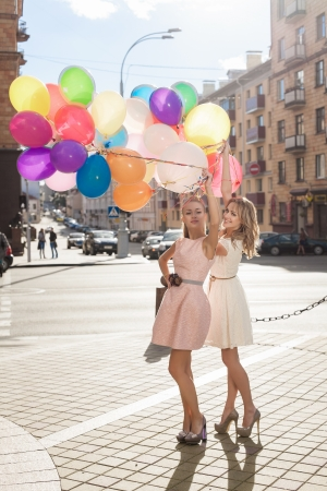 Two young blond women with colorful balloons, urban scene, outdoors photo