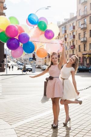 thời trang: Hai người phụ nữ tóc vàng trẻ cầm bóng latex đầy màu sắc, cảnh đô thị, ngoài trời