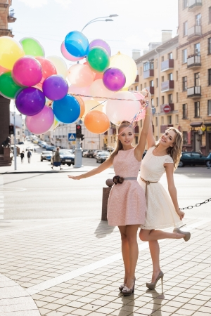 Two young blond women holding colorful latex balloons, urban scene, outdoors