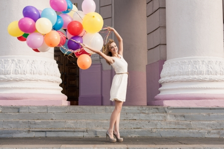 street fashion: Young woman with colorful latex balloons keeping her dress, urban scene, outdoors Stock Photo
