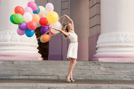 Young bridal with colorful latex balloons keeping her dress, urban scene, outdoors photo