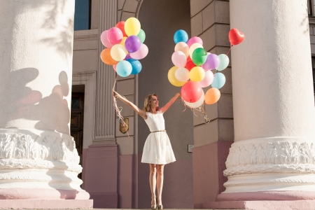 windy city: Young girl with colorful latex balloons keeping her dress, urban scene, outdoors