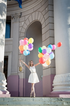 Young sexy woman with colorful latex balloons keeping her dress, urban scene, outdoors photo