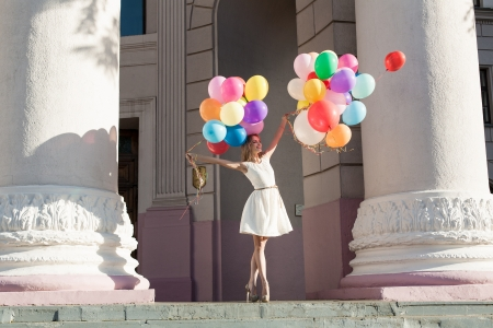 windy city: Young sensual woman with colorful latex balloons keeping her dress, urban scene, outdoors Stock Photo