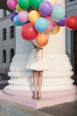 Girl with colorful latex balloons keeping her dress, urban scene, outdoors photo