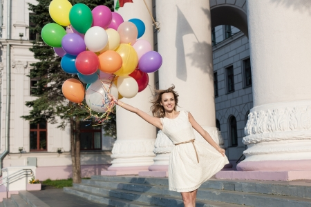 windy city: Happy woman with colorful latex balloons keeping her dress, urban scene, outdoors