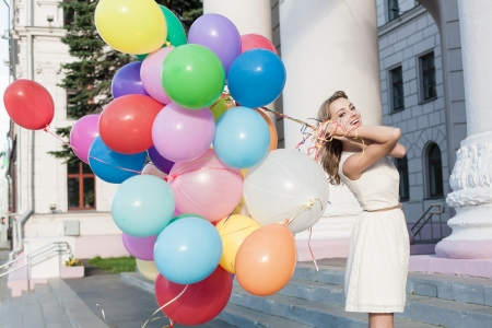 street fashion: Happy young woman with colorful latex balloons keeping her dress, urban scene, outdoors Stock Photo