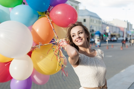 woman fashion: Happy young woman with colorful latex balloons keeping her dress, urban scene, outdoors Stock Photo