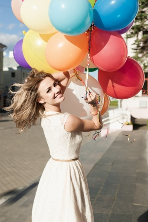 weather balloon: Happy young woman with colorful latex balloons keeping her dress, urban scene, outdoors Stock Photo