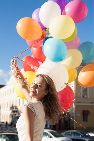 windy city: Happy young woman with colorful latex balloons keeping her dress, urban scene, outdoors Stock Photo