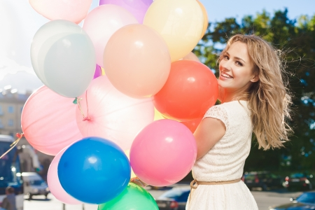 keeping: Happy young woman with colorful latex balloons keeping her dress, urban scene, outdoors Stock Photo