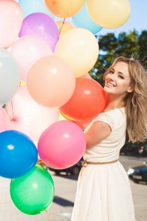 windy city: Mujer joven feliz con globos de l�tex de colores manteniendo su vestido, escena urbana, al aire libre Foto de archivo