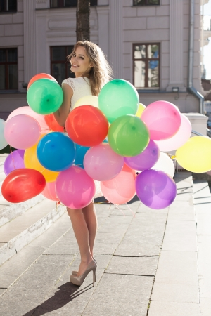 latex woman: Happy young woman with colorful latex balloons keeping her dress, urban scene, outdoors Stock Photo
