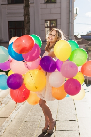 Happy young woman with colorful latex balloons keeping her dress, urban scene, outdoors Stock Photo - 15574974