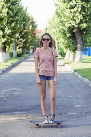 Portrait of a woman with a skateboard on street,\ outdoors