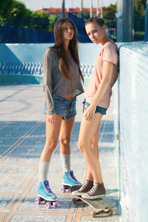 Two young active women in roller park, outdoors photo