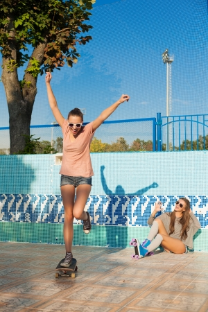 Two young active women skating in roller park, outdoors photo