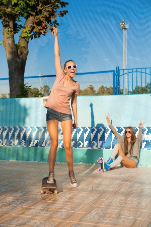 Two young sensual girls skating in roller park, outdoors Stock Photo - 15608267