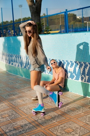 Two young sensual active women in roller park, outdoors photo
