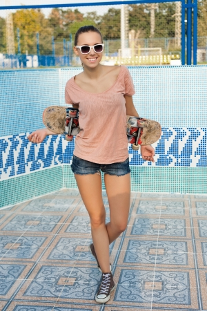 Portrait of a woman with a skateboard in her hand, outdoors photo
