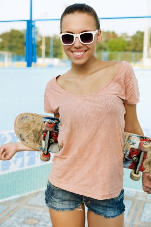 Portrait of a young woman with a skateboard in her hand, outdoors Stock Photo - 15608259