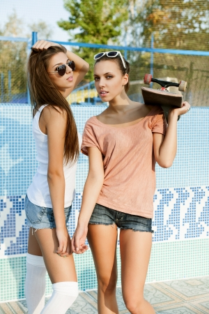 skate board: Two young sensual friends in piscina, outdoors