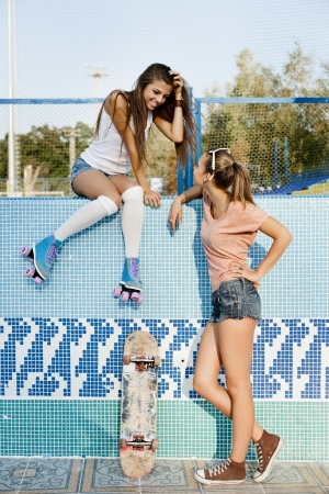 Two young sensual girls talking in piscina, outdoors photo