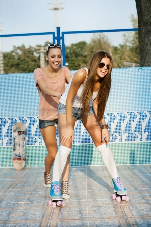 human sexual activity: Two young sensual women skating in piscina, outdoors