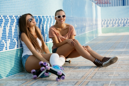 Two young skateboarding and roller skating girl friends sitting in empty swimming pool, outdoors photo