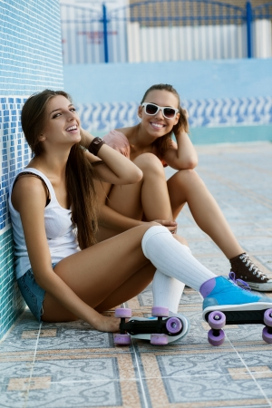 sexual activities: Two young skateboarding and roller skating girl friends sitting and laughing in empty swimming pool, outdoors