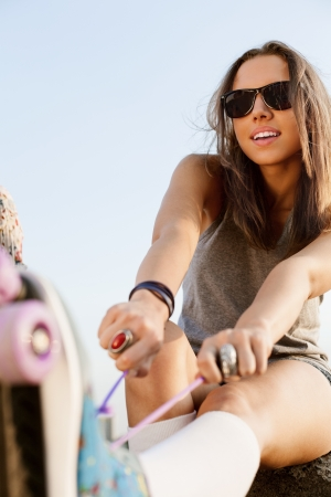 happy young brunette woman fastening the roller skates and is getting ready to ride  in the park, outdoors photo