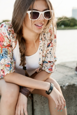 woman street: Portrait of a Young caucasian woman sitting on the bank of river. Outdoors