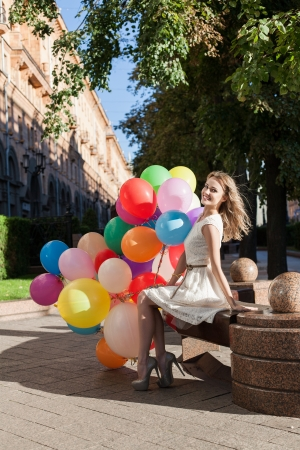 Happy young woman with colorful latex balloons keeping her dress, urban scene, outdoors Stock Photo - 15785730