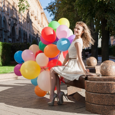 sexy birthday: Happy young woman with colorful latex balloons keeping her dress, urban scene, outdoors Stock Photo