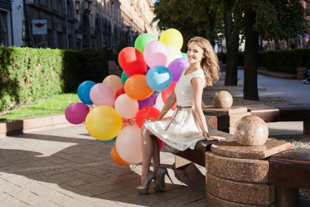 Happy young woman with colorful latex balloons keeping her dress, urban scene, outdoors photo
