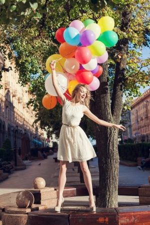 Happy young woman with colorful latex balloons keeping her dress, urban scene, outdoors Stock Photo