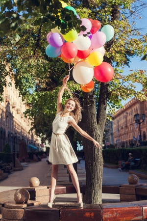 Happy young woman with colorful latex balloons keeping her dress, urban scene, outdoors Stock Photo - 15785733