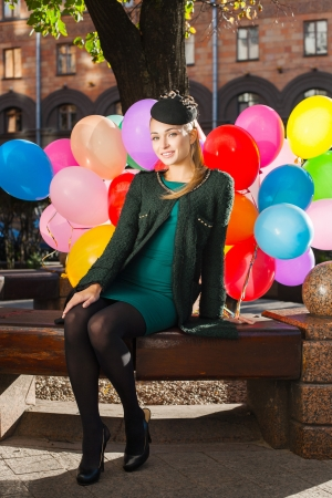 Pretty young woman with colorful latex balloons sitting in park, urban scene, outdoors Stock Photo - 15785741