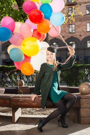 sexy bride: Happy young woman with colorful latex balloons sitting in park, urban scene, outdoors Stock Photo