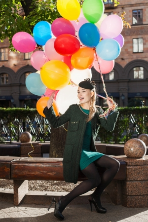 Happy young woman with colorful latex balloons sitting in park, urban scene, outdoors photo