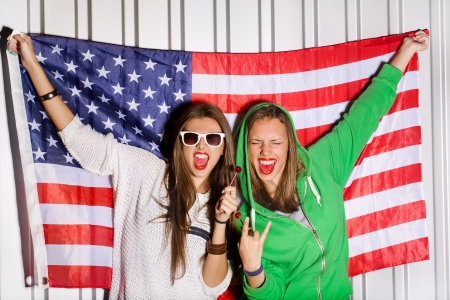 state of mood: two beautiful young women holding national usa flag in background, sucking a lollipop, outdoors