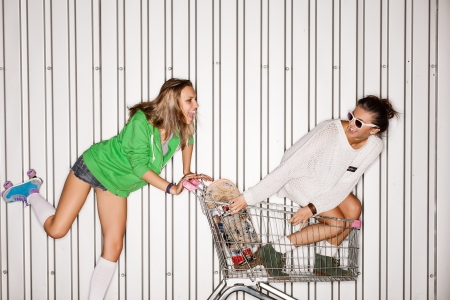 full shopping cart: Happy two young women with shopping cart. outdoors Stock Photo