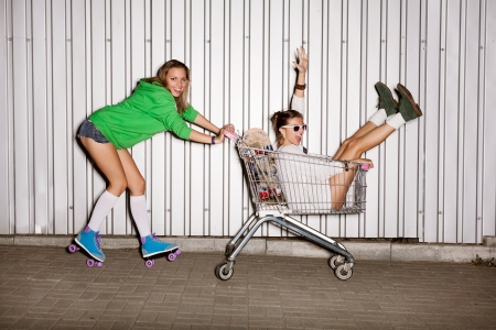 Happy two naughty women with shopping cart. outdoors photo